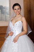 Portrait of beautiful bride with adorable smile, veil and fashionable wedding dress — Stock Photo