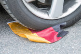 German Soccer Flag under Tire with Tire Tracks — Stock Photo