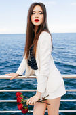 Fashion portrait of stunning model posing outdoor near deep blue sea water. — Stock Photo