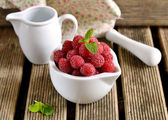 Raspberries in a white mortar jug with a pestle — Stock Photo