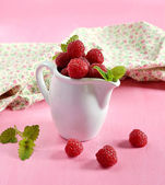 Ripe raspberries in a white jug with mint — Stockfoto