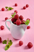 Raspberries in a white jug with mint — Stock Photo