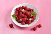 Raspberries in a white plate with mint — Stock Photo