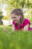 Girl lying on green grass — Stock Photo