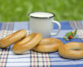 Bagels and mug with milk on tartan tablecloth — Stock Photo