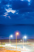 Night view of the sea with three colorful electric poles — Foto Stock