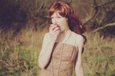 Redhead woman eating an apple — Stock Photo