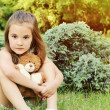 Beautiful little girl holding toy and sitting outdoors on the gr — Stock Photo