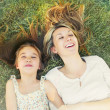 Happy little girl and her mother having fun on the grass in sunn — Stock Photo #49785991