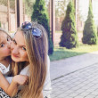 Little cute girl kissing her beautiful mum outdoor in the park — Stock Photo #49786093