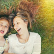 Cute little girl and her mother having fun on the grass in sunny — Stock Photo #49786133