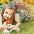 Cute smiling little girl holding teddy bear and sitting on the g — Stock Photo #49786149