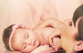 Young beautiful mother holding with love her little cute sleepin — Stock Photo