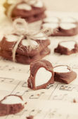 Heart shape chocolate cookies on old music notes — Stock Photo