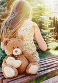 Little girl sitting back with teddy bear on the bench in sun bea — Stock Photo
