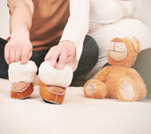 Hands of pregnant couple with little boots for baby — Stock Photo