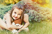 Cute smiling little girl holding teddy bear and sitting on the g — Stock Photo
