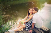 Sensual romantic couple in love on pier at the lake in sunny day — Stock Photo