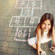 Beautiful cheerful little girl playing hopscotch on playground — Stock Photo #51213111