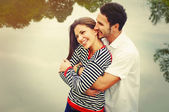 Happy romantic wide smile couple in love at the lake outdoor on — Stock Photo