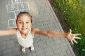 Cheerful little girl playing hopscotch on playground  — Stock Photo