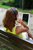 Girl using tablet outdoors — Stock Photo