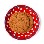 Ginger cookies on red white dotted dish isolated on white backgr — Stock Photo