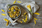 Summer flowers pasta with seed and petals flowers and yellow spices on rustic background — Photo