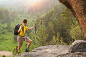 Backpacker go up mountain — Stock Photo