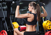 Woman exercising on weightlifting machine — Stock Photo