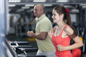 Sportive woman and man are jogging treadmill — Stockfoto