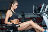 Sportive woman doing exirsise on cycling simulator — Stock Photo