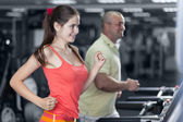 Sportive woman and man are jogging treadmill — Stock Photo