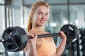 Woman doing workout with barbell — Stock Photo