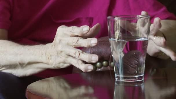 Verre et mains arthritiques — Vidéo