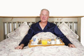 Surprised Man with Breakfast in Bed — Stock Photo