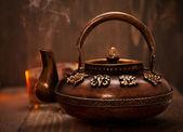 Antique iron hot tea pot on dark wooden background — Stock Photo