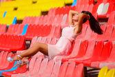 Asian model posing at the stadium sitting on bright seats — Stock Photo