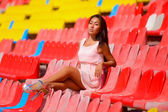 Asian model posing at the stadium sitting on bright seats — Foto de Stock
