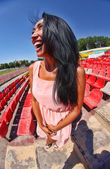 Portrait of Asian model posing at the stadium standing on the bright seats — Stock Photo