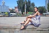 Belle jeune femme posant assis partiellement humide sur le paysage urbain — Photo