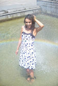 Woman in a wet dress and wet brown hair posing on the background of the rainbow from the fountain — Stock Photo