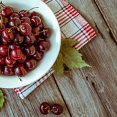 Fresh ripe cherries on a dark wooden board. Toning in vintage — Stock Photo
