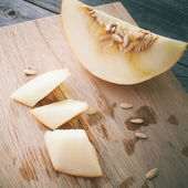 Slices of honeydew melon on gray wooden table — Stock Photo