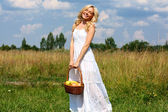 Beautiful young blond woman in a white sundress — Stock Photo
