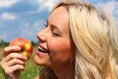 Dívka kousání červené jablko — Stock fotografie