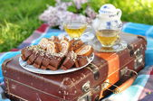 Delicious cakes with fillings with two cups of tea on a suitcase — Stock Photo