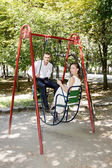 Bride and groom on a swing — Stock Photo