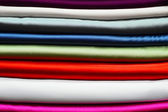 Stack of colourful folded fabric for use in sewing clothing — Stock Photo