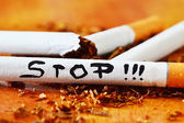 Cigarettes with a brown filter close up and stop message text — Stock Photo